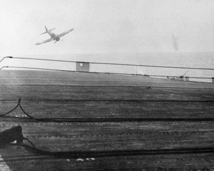 750px-USS_White_Plains_attack_by_Tokkotai_unit_25.10.1945_kk1a 1944年10月25日、護衛空母「ホワイト・プレーンズ」に肉迫する第1神風特別攻撃隊「敷島隊」の零戦。この直後、対空砲火によって右翼に被弾、撃墜された。