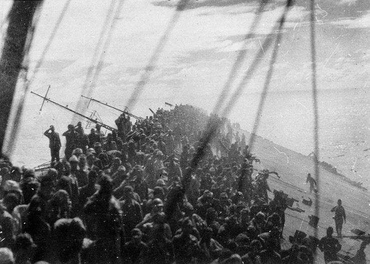 Lowering_the_flag_on_Zuikaku レイテ沖海戦でアメリカ軍の攻撃を受け沈没しつつある空母瑞鶴(14時14分沈没)。