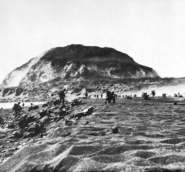 硫黄島に上陸して進撃するアメリカ海兵隊。奥に見えるのが摺鉢山