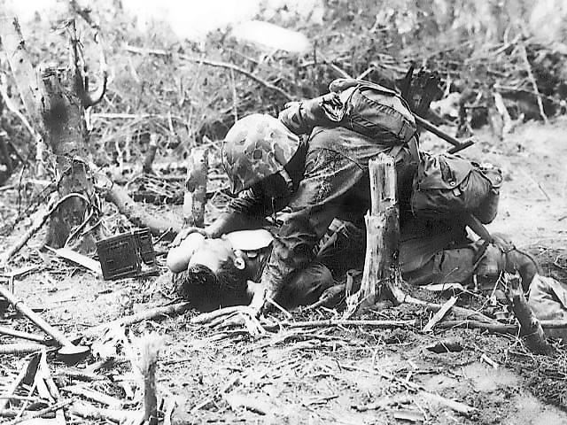 ペリリュー島で負傷した戦友に水を飲ませる米海兵隊員
