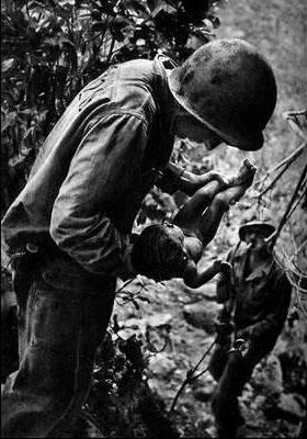 サイパンで死体で折り重なった洞窟から赤ん坊を救出するアメリカ軍兵士